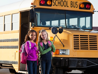 Two girls with school bus