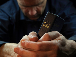 praying man holding bible